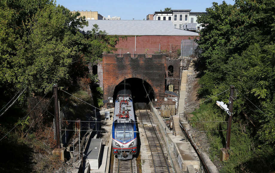 In this Sept. 15, 2015 photo, an Amtrak train emerges from the Baltimore and Potomac Tunnel in Baltimore. As state and federal officials look for an estimated $15 billion for a new train tunnel between New York and New Jersey, passengers up and down the rail line known as the Northeast Corridor contend with regular disruptions caused by track configurations and infrastructure dating to the time of the Model T, or earlier.(AP Photo/Patrick Semansky)