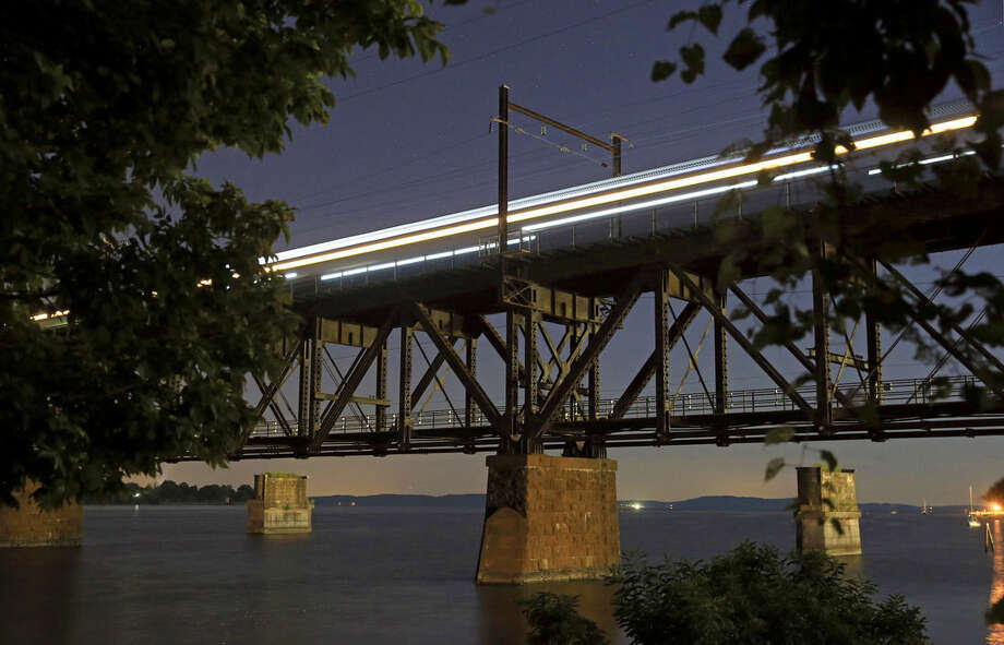 In this Aug. 25, 2015 photo, an Amtrak train passes over the Susquehanna River rail bridge between Perryville and Havre De Grace, Md. As state and federal officials look for an estimated $15 billion for a new train tunnel between New York and New Jersey, passengers up and down the rail line known as the Northeast Corridor contend with regular disruptions caused by track configurations and infrastructure dating to the time of the Model T, or earlier. (AP Photo/Patrick Semansky)