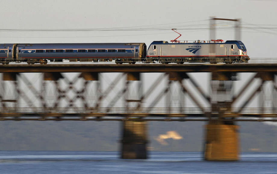 In this Aug. 25, 2015 photo, an Amtrak train passes over the Susquehanna River rail bridge between Perryville and Havre De Grace, Md. As state and federal officials look for an estimated $15 billion for a new train tunnel between New York and New Jersey, passengers up and down the rail line known as the Northeast Corridor contend with regular disruptions caused by track configurations and infrastructure dating to the time of the Model T, or earlier.(AP Photo/Patrick Semansky)