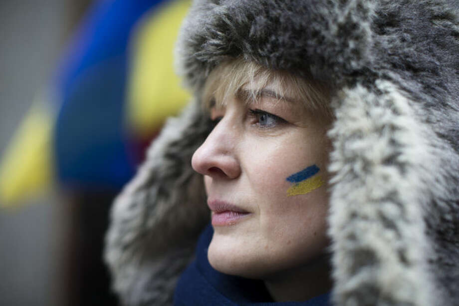 """Valentina Bardakova, a demonstrator against Russian military actions in Ukraine, attends a rally near Times Square, Sunday, March 2, 2014, in New York. Western powers are prepared """"to go to the hilt"""" to isolate Russia for its military incursion into Ukraine, """"an incredible act of aggression"""" that may lead to visa bans, asset freezes, trade and investment penalties, and a boycott of a Russian-hosted economic summit of global powers in June, Secretary of State John Kerry said Sunday. (AP Photo/John Minchillo)"""