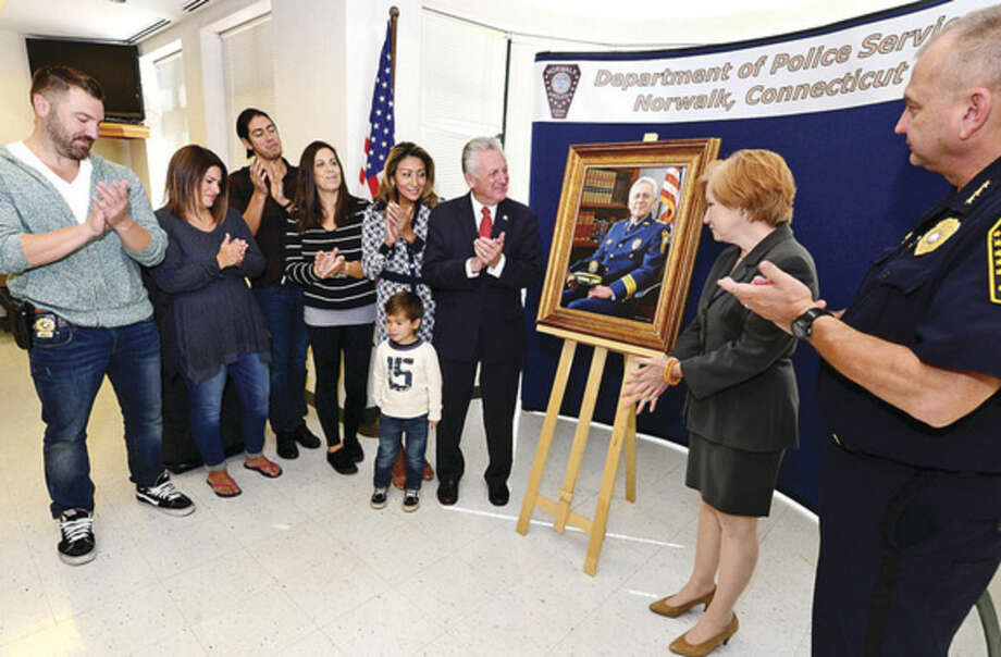 Hour photo / Erik Trautmann Norwalk Mayor Harry Rilling and his family, son, Stephen Rilling, daughter-in-law, Melanie Werheim, daughter, Kylee Rilling, grandson, Weston Rilling, wife, Lucia Rilling, artist Gini Frank Fischer, and Police Chief Thomas Kuhalwik, unveil a portrait of Rilling in his former role as Norwalk Police Chief during a brief ceremony at Police Headquarters Tuesday.