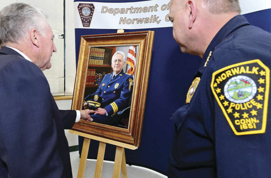 Hour photo / Erik Trautmann Norwalk Mayor Harry Rilling and Police Chief Thomas Kuhalwik admire the portrait of Rilling in his former role as Norwalk Police Chief during a brief ceremony at Police Headquarters Tuesday.