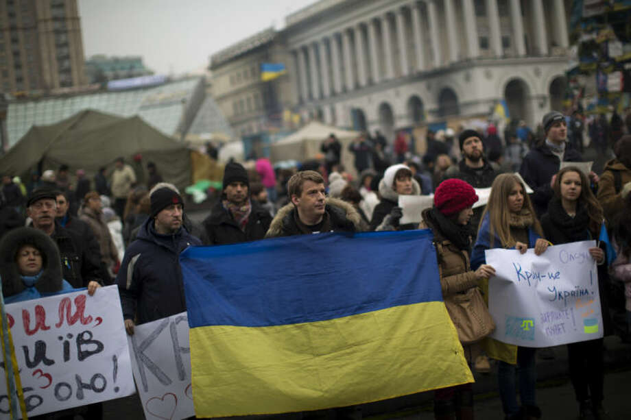 Protesters, one them holding an Ukraine flag, demonstrate against the military intervention of Russia in Crimea as they gather in Kiev's Independence Square, the epicenter of the country's current unrest, Ukraine, Saturday, March 1, 2014. Russia's parliament granted President Vladimir Putin permission to use the country's military in Ukraine and also recommended Saturday that Moscow's ambassador be recalled from Washington over comments made by President Barack Obama. The unanimous vote in an emergency session formalized what Ukrainian officials described as an invasion of Russian troops in the strategic region of Crimea. With pro-Russian protests breaking out in other parts of Ukraine, Moscow now could send its military elsewhere in Ukraine. (AP Photo/Emilio Morenatti)