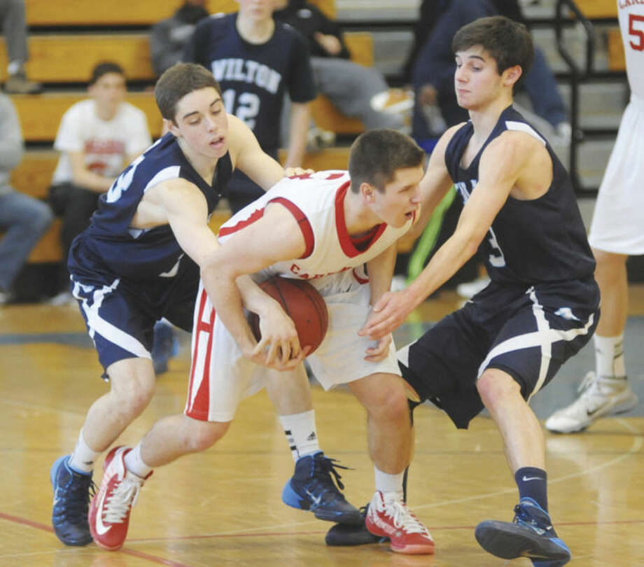 Hour photo/John Nash - Wilton's Matt Shifrin, left, and Eric Houska, right, trap Greenwich's Tom Povinelli during the third quarter of Saturday's FCIAC boys basketball quarterfinal in Fairfield. Greenwich topped the Warriors 70-62.
