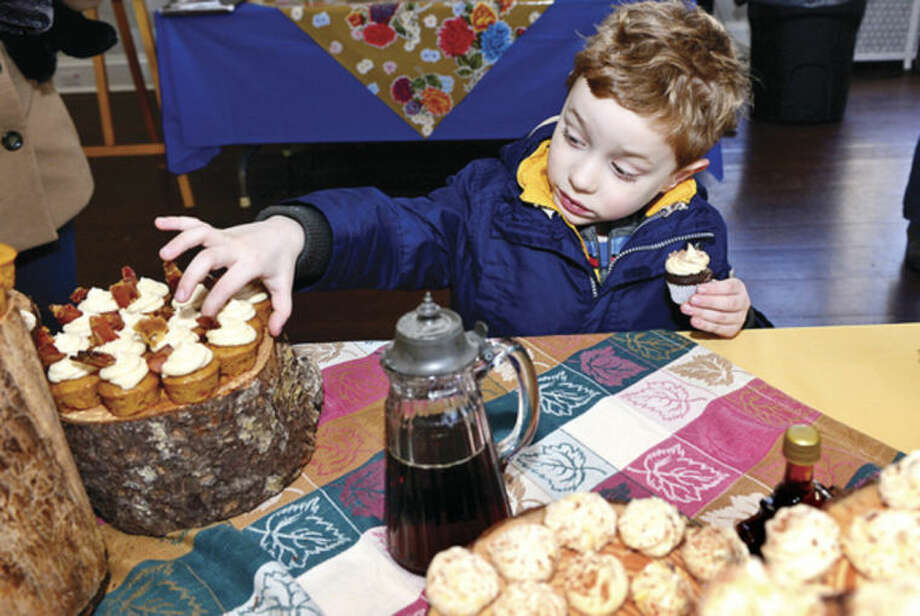 Hour photo / Erik Trautmann 4 year old Joseph Fraser tries Evan Cassidy's Sweet Potato Cupcake with Maple Butter Cream in First County Bank's Teen Chefs Challenge event at the Stamford Museum & Nature Center during this year's Maple Sugar Festival Weekend. On Saturday, March 1, the teen chefs will compete in an exciting competition to create the best tasting recipe, as judged by the public, using maple syrup as an ingredient.