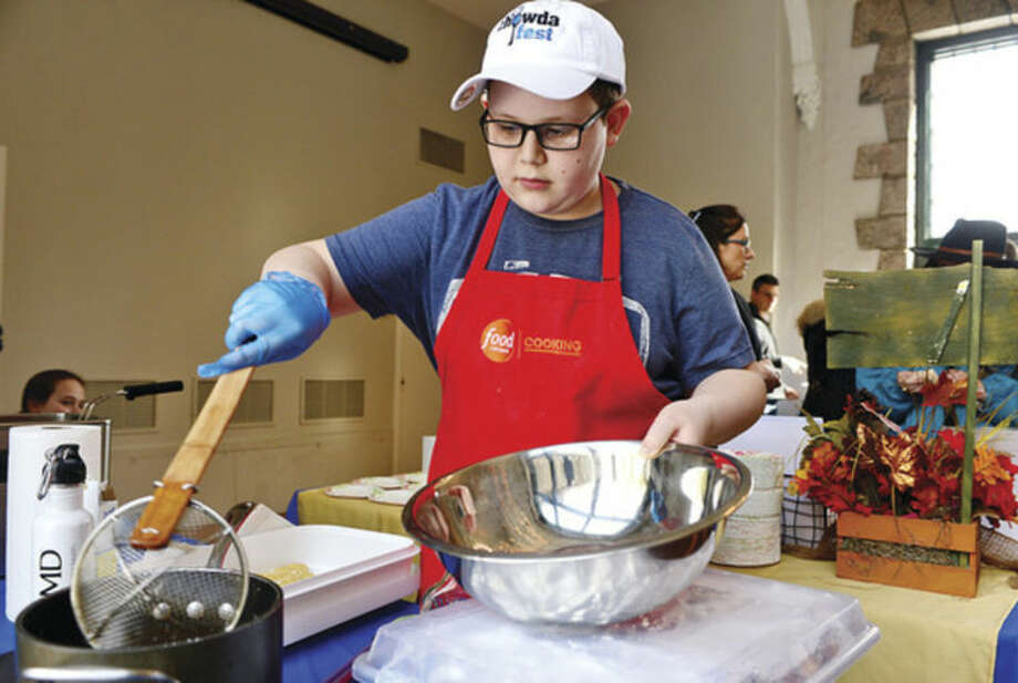 Hour photo / Erik Trautmann Hunter Zampa competes in First County Bank's Teen Chefs Challenge event at the Stamford Museum & Nature Center during Saturday's Maple Sugar Festival. The teen chefs compete in a competition to create the best tasting recipe, as judged by the public, using maple syrup as an ingredient.