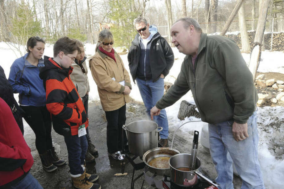 Hour photos / Matthew VinciAllan Klumac, volunteer at the Stamford Museum and Nature Center, demonstrates the process involved in making maple sugar at the adult workshop held on Sunday.
