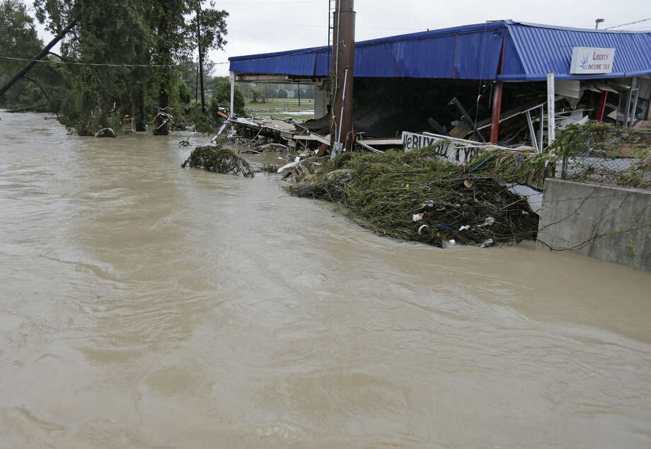 Floodwaters rise over the banks of Gills Creek, destroying several businesses in Columbia, S.C., Monday, Oct. 5, 2015. Days of torrential rains kept much of South Carolina and its capital gripped by floodwaters early Monday . (AP Photo/Chuck Burton)