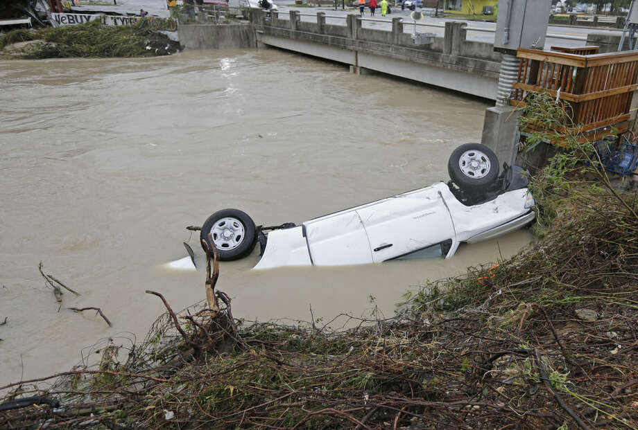 A pickup truck rests against the side of Gills Creek near a bridge in Columbia, S.C., Monday, Oct. 5, 2015. Days of torrential rains kept much of South Carolina and its capital gripped by floodwaters early Monday. (AP Photo/Chuck Burton)