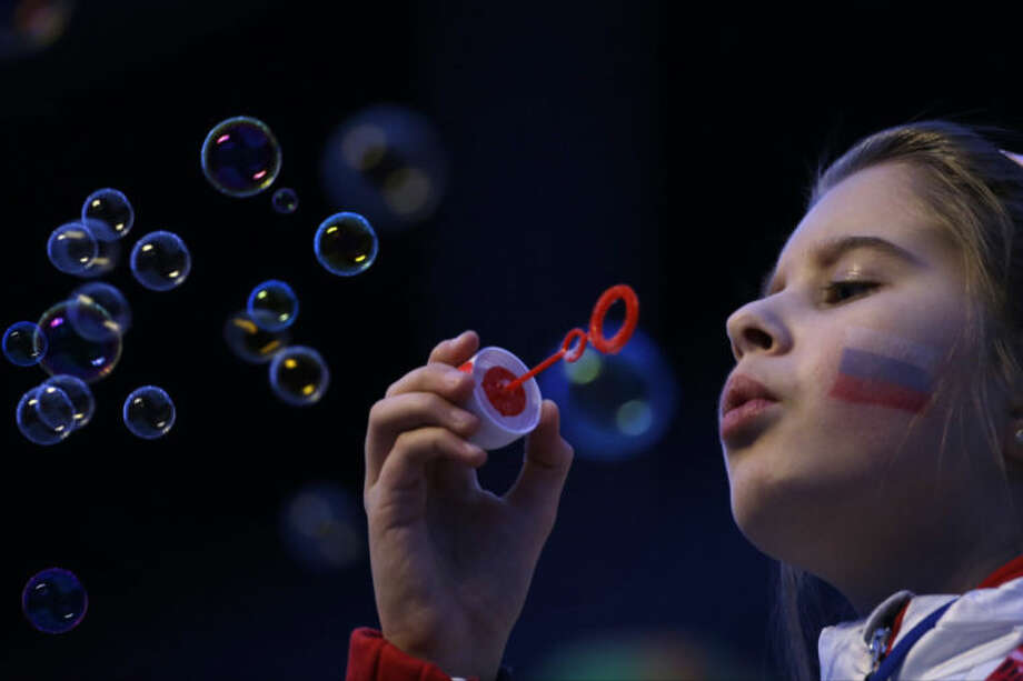 A girl with a Russian flag painted on her face blows bubbles as she waits for the start of the closing ceremony of the 2014 Winter Olympics in Sochi, Russia, Sunday, Feb. 23, 2014. (AP Photo/Gregorio Borgia)