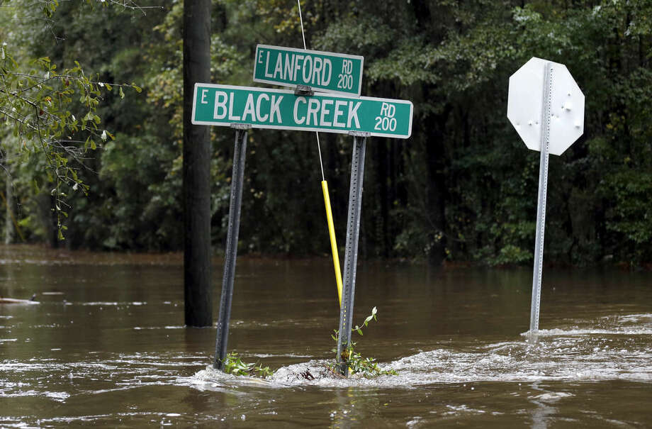 Street signs are surrounded by floodwater from Black Creek in Florence, S.C., Monday, Oct. 5, 2015 as flooding continues following several days of rain. (AP Photo/Gerry Broome)