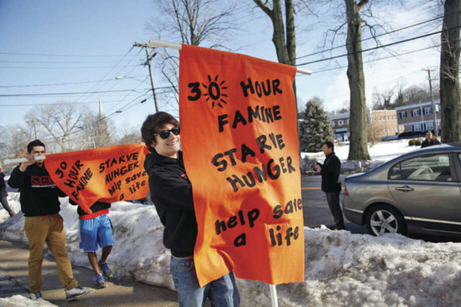 Hour photos / Danielle CallowayAbove, Mike Falbo holds a sign while walking through Norwalk to honor Night Walkers of Uganda during St. Philip Church's 30-hour famine Saturday morning. Below, students hold signs while walking through Norwalk to honor Night Walkers of Uganda.