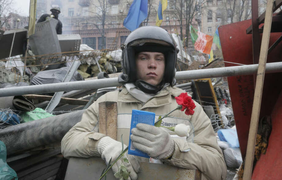 CORRECTS DATE- An activist holds flowers and a chocolate as he guards one of the barricades heading to Kiev's Independence Square, the epicenter of the country's recent unrest, Ukraine, on a mourning day Sunday, Feb. 23, 2014. Official reports say 82 persons were killed in severe clashes between opposition protesters and riot police. Hundreds of thousands of the Ukrainians came Sunday to Independence Square to pay tribute to the victims. A top Ukrainian opposition figure assumed presidential powers Sunday, plunging Ukraine into new uncertainty after a deadly political standoff Ñ and boosting long-jailed Yulia Tymoshenko's chances at a return to power.(AP Photo/Efrem Lukatsky)