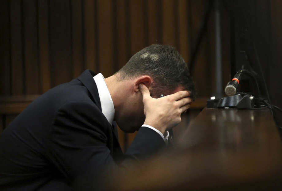 Oscar Pistorius, cradles his head in his hands as he listens to ballistic evidence being given in the court during his murder trial in Pretoria, South Africa, Wednesday, March 19, 2014. Pistorius is on trial for the murder of his girlfriend Reeva Steenkamp on Valentine's Day in 2013. (AP Photo/Themba Hadebe, Pool)