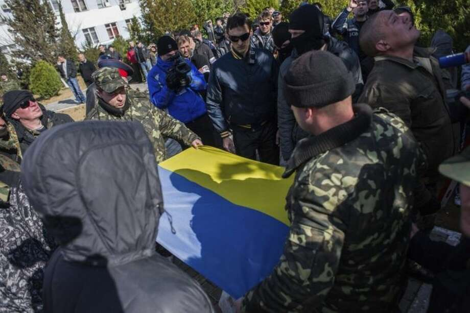 Ukrainian soldiers fold the Ukrainian flag, which was removed by a Crimean pro- Russian self-defense force at the Ukrainian Navy headquarters in Sevastopol, Crimea, Wednesday, March 19, 2014. An Associated Press photographer said several hundred militiamen took down the gate and made their way onto the base. They then raised the Russian flag on the square by the headquarters. The unarmed militia waited for an hour on the square before the move to storm the headquarters. Following the arrival of the commander of the Russian Black Sea fleet, the Crimeans took over the building. (AP Photo/Andrew Lubimov)