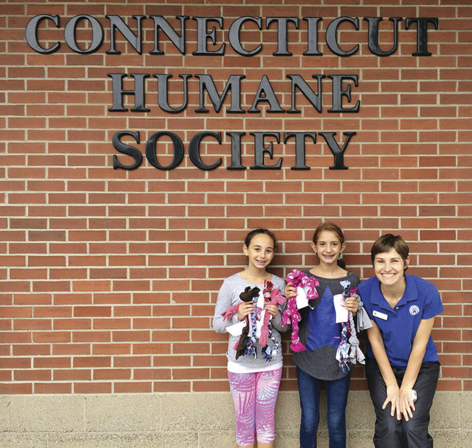 Contributed photoNorwalk Girl Scouts Mia Piacenza and Morgan Minoff, along with Connecticut Humane Society district manager Bliss Kern, show off the dog pull toys they made recently at the society's Westport location.