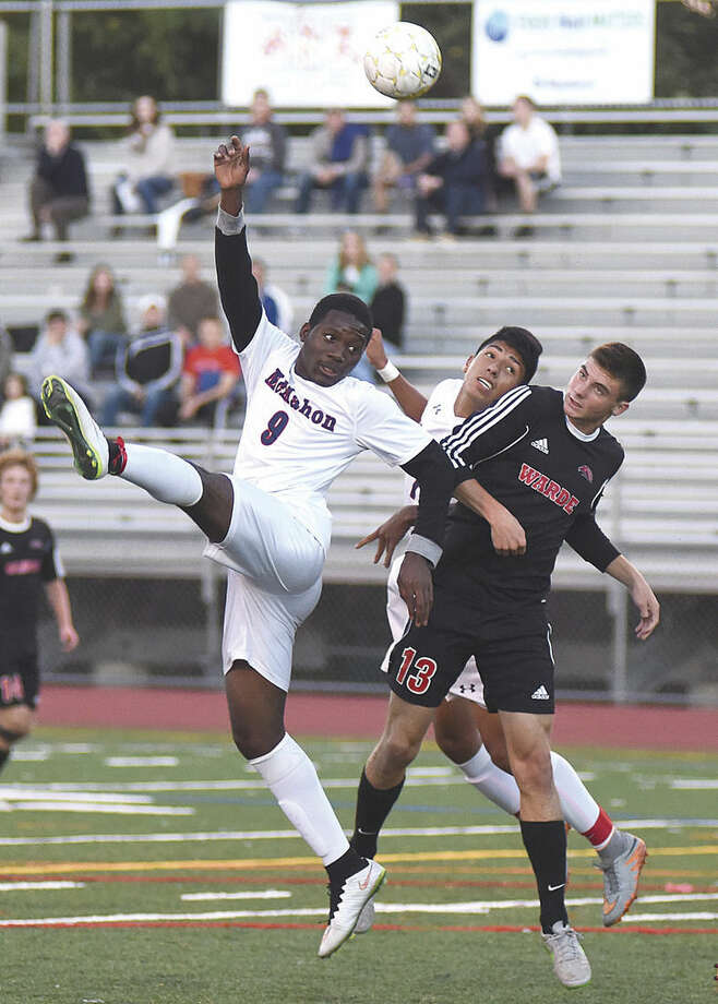 Hour photo/John NashBrien McMahon's Junior Dorsainvil (9) and Afa Reyes, rear, try to win a ball out of the air against Fairfield Warde's Joey Ciccarelli during the first half of Monday's FCIAC boys soccer game at Casagrande Field in Norwalk.