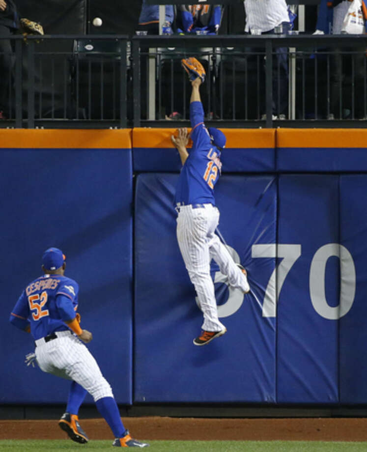 New York Mets left fielder Yoenis Cespedes watches as center fielder Juan Lagares (12) can't reach Adrian Gonzalez's solo home run off Bartolo Colon in the seventh inning of baseball's Game 3 of the National League Division Series against the Los Angeles Dodgers, Monday, Oct. 12, 2015, in New York. (AP Photo/Kathy Willens)