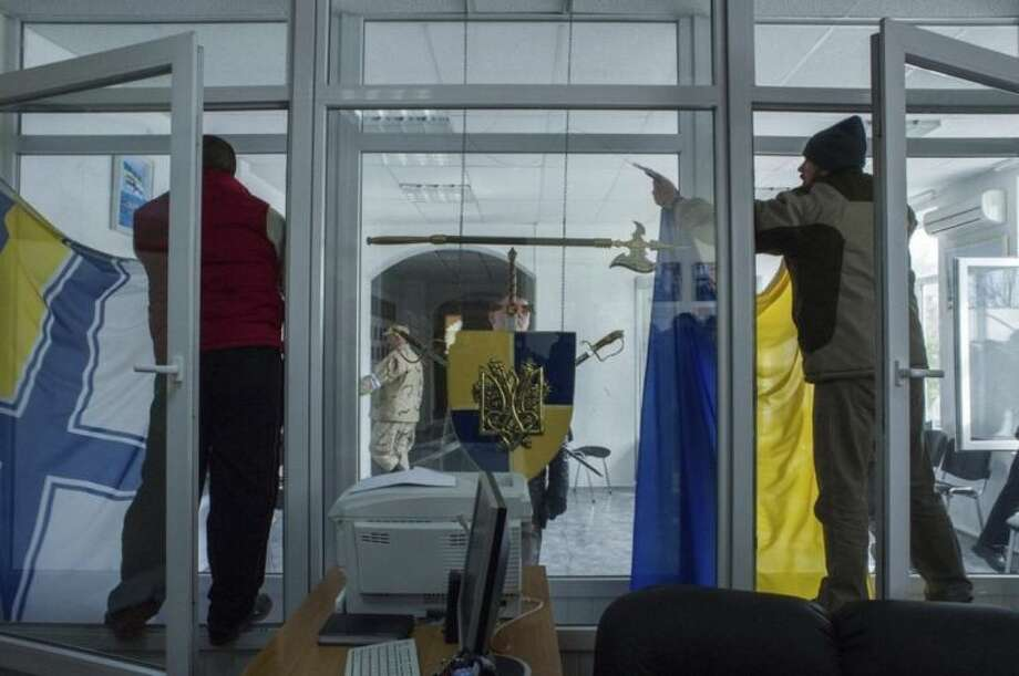 Members of a Pro-Russian self-defense force remove a Ukrainian Navy flag, left, as the other removes the Ukrainian flag at the Ukrainian Navy headquarters in Sevastopol, Crimea, Wednesday, March 19, 2014. An Associated Press photographer said several hundred militiamen took down the gate and made their way onto the base. They then raised the Russian flag in the square by the headquarters. The unarmed militia waited for an hour on the square before the move to storm the headquarters. Following the arrival of the commander of the Russian Black Sea fleet, the Crimeans took over the building. (AP Photo/Andrew Lubimov)