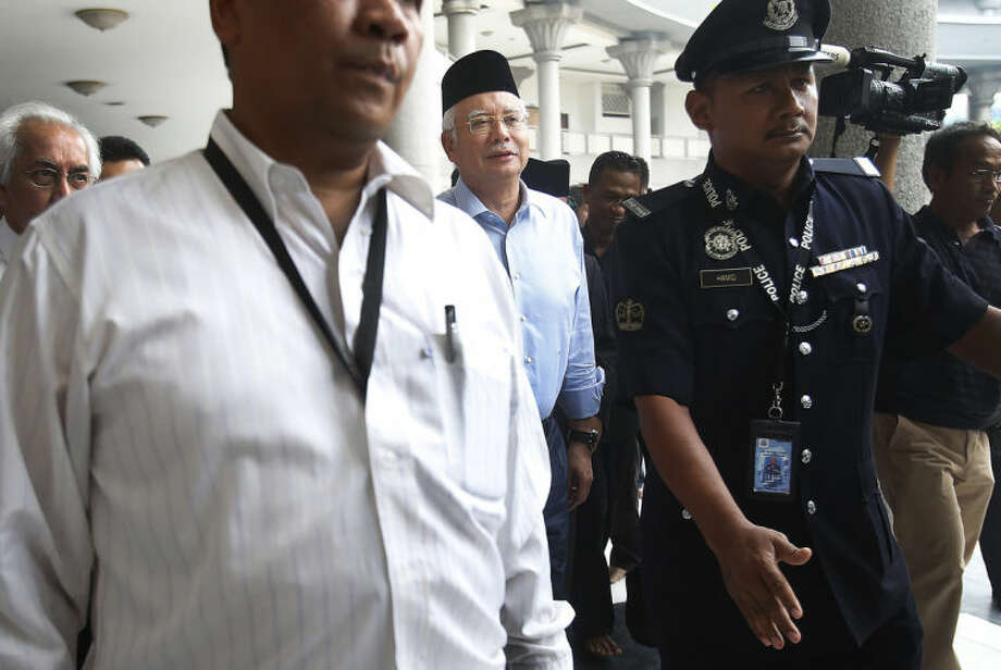 Malaysian Prime Minister Najib Razak, center, arrives at the Kuala Lumpur International Airport Mosque for Friday prayers where a special prayer was offered for the missing Malaysia Airlines flight MH370, Friday, March 14, 2014 in Sepang, Malaysia. Vietnam says it has downgraded but not stopped its search for the missing jetliner in the South China Sea and has been asked by Malaysian authorities to consider sending planes and ships to the Strait of Malacca. The statement Friday is a sign that the focus of the search effort is switching to the west of Malaysia, to the strait and further west into the Indian Ocean. (AP Photo/Wong Maye-E)