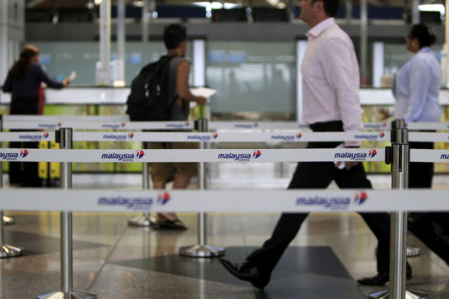 Passengers walk to check in at Malaysia Airlines counters at Kuala Lumpur International Airport in Sepang, Malaysia, Tuesday, March 18, 2014. Checks into the background of all the Chinese nationals on board the missing Malaysian jetliner have uncovered no links to terrorism, the Chinese ambassador in Kuala Lumpur said Tuesday. (AP Photo/Lai Seng Sin)