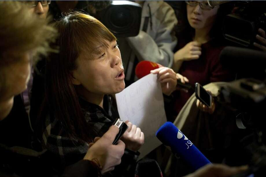 """A relative of a Chinese passenger aboard the missing Malaysia Airlines Flight MH370 holds a paper which reads """"Hunger strike protest, Respect life, Return my relative, Don't want become victim of politics, Tell the truth"""" as she speaks to the media outside a hotel ballroom after attending a briefing held by the airlines' officials in Beijing, China, Tuesday, March 18, 2014. Families of the passengers aboard the missing plane decided to organize a hunger strike to express their anger and disappointment at the handling of the situation by authorities. They decided on the action after a daily morning meeting with two officials from Malaysia Airlines. The plane has been missing since March 8, and contradictory information plus the fact there has been no sign of the plane has left family members frustrated. (AP Photo/Andy Wong)"""