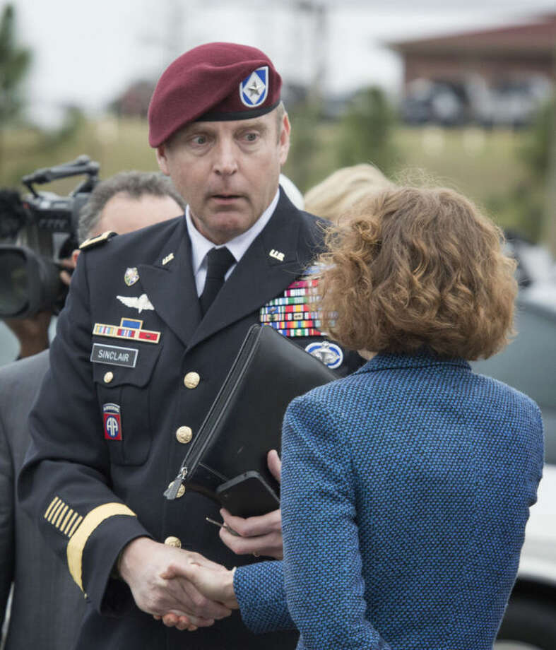 Brig. Gen. Jeffrey Sinclair shakes hands with his defense attorney Ellen C. Brotman outside the Fort Bragg, N.C. courthouse, Monday, March 17, 2014. Sinclair, who admitted to improper relationships with three subordinates appeared to choke up as he told a judge that he'd failed the female captain who had leveled the most serious accusations against him. (AP Photo/The Fayetteville Observer, Johnny Horne)