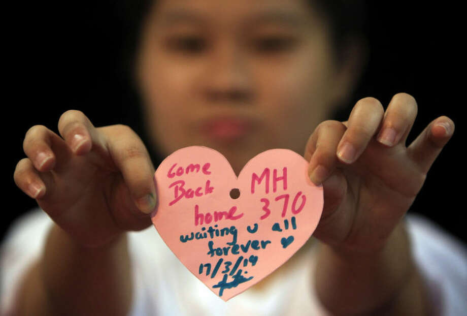 A woman holds a heart shaped paper with messages for passengers aboard a missing Malaysia Airlines plane, as she poses for a photo during an event in Kuala Lumpur, Malaysia, Monday, March 17, 2014. Authorities now believe someone on board the Boeing 777 shut down part of the aircraft's messaging system about the same time the plane with 239 people on board disappeared from civilian radar. But an Inmarsat satellite was able to automatically connect with a portion of the messaging system that remained in operation, similar to a phone call that just rings because no one is on the other end to pick it up and provide information. No location information was exchanged, but the satellite continued to identify the plane once an hour for four to five hours after it disappeared from radar screens. (AP Photo/Lai Seng Sin)