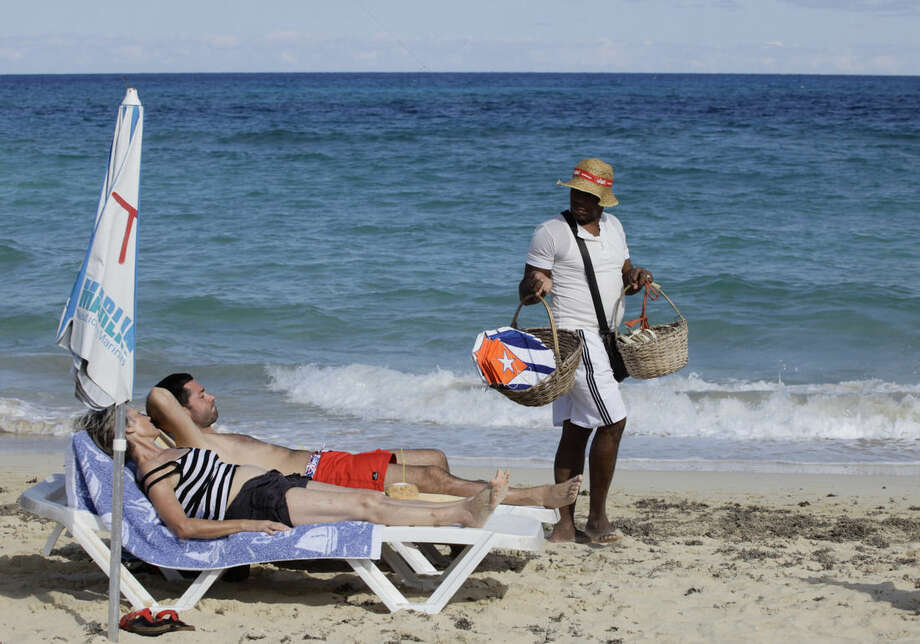 "In this Dec. 19, 2014 photo, tourists sunbathe as a vendor sells kites decorated with Cuba's flag on a beach near Havana, Cuba. The easing of tourism regulations is a gamble for both the U.S. and Cuba. Obama said Wednesday that people-to-people travel was a way to ""empower the Cuban people."" At the same time, a U.S. tourism surge could funnel sorely needed cash to a tourism industry run mostly by what Obama described Friday as ""a regime that represses its people."" (AP Photo/Desmond Boylan)"