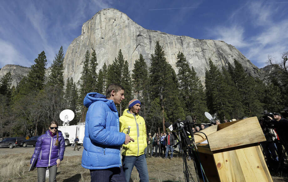 Tommy Caldwell, left, and Kevin Jorgeson approach a podium as they prepare to speak during a news conference Thursday, Jan. 15, 2015, in El Capitan meadow in Yosemite National Park, Calif. The two climbers became the first in the world to use only their hands and feet to scale El Capitan, in background, a sheer granite face in California's Yosemite National Park. (AP Photo/Ben Margot)