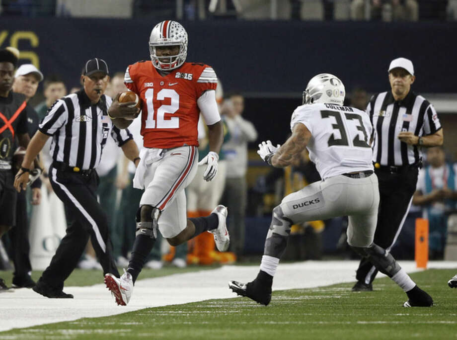 Ohio State's Cardale Jones (12) runs in front of Oregon linebacker Tyson Coleman (33) during the first half of the NCAA college football playoff championship game Monday, Jan. 12, 2015, in Arlington, Texas. (AP Photo/Brandon Wade)