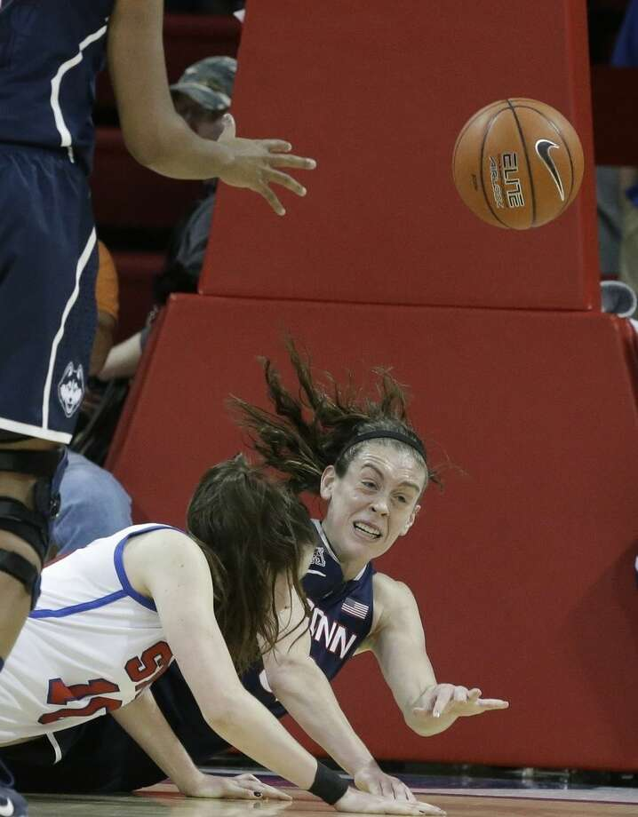 Connecticut forward Breanna Stewart (30) gets a pass off as falls with SMU forward Keely Froling (11) during the first half of an NCAA college basketball game, Sunday, Jan. 11, 2015, in Dallas. (AP Photo/LM Otero)