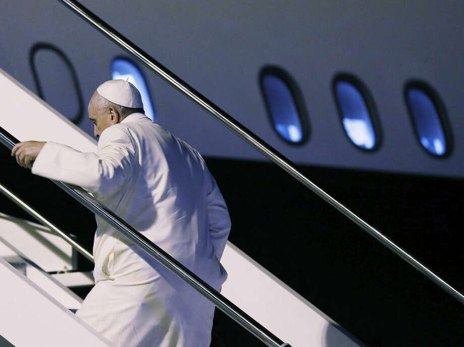 Pope Francis boards the airplane on the occasion of his trip to Sri Lanka and Philippines, at Rome's Fiumicino International Airport, Monday, Jan. 12, 2015. The Pontiff embarks on his second Asian pilgrimage visiting Sri Lanka and the Philippines exactly 20 years after St. John Paul II's record-making visit to two countries with wildly disparate Catholic populations. Francis will make headlines of his own, drawing millions of faithful in the Philippines and treading unchartered political waters following Sri Lanka's remarkable electoral upset this week.(AP Photo/Gregorio Borgia)