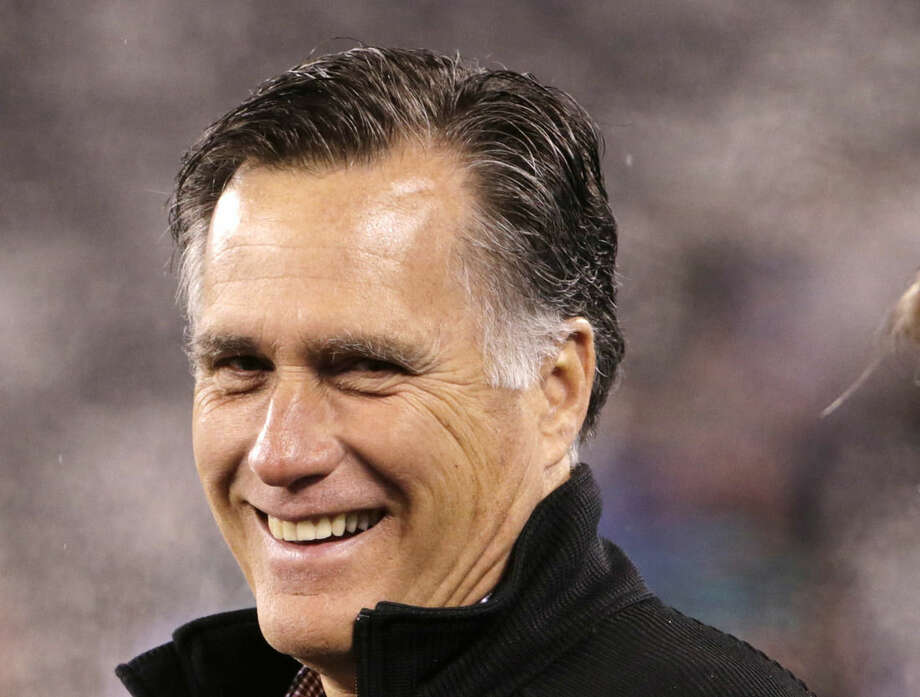 In this photo taken Dec. 1, 2014. for Republican presidential canadiate Mitt Romney smiles on the field before an NFL football game between the New York Jets and the Miami Dolphins in East Rutherford, N.J. Mitt Romney is reaching out to former staff and supporters as he considers a third run for president. Romney and his wife, Ann, phoned former backers in the early voting states of New Hampshire and Iowa to gauge their support over the weekend. (AP Photo/Julio Cortez)