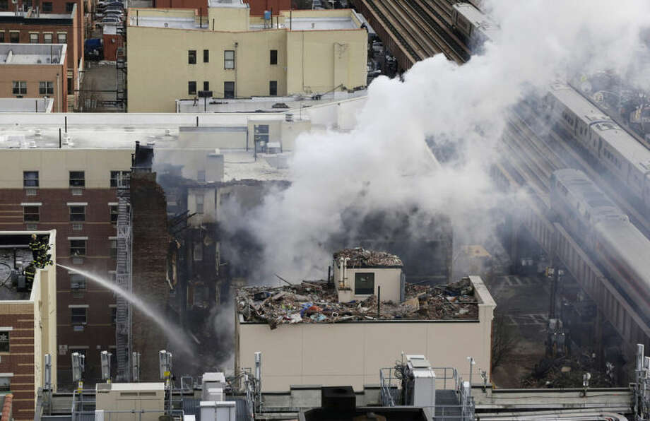 Firefighters, lower left, pour water on the site of a building explosion, as a Metro-North commuter train, right, passes the site on Thursday, March 13, 2014 in New York. Rescuers working amid gusty winds, cold temperatures and billowing smoke pulled four additional bodies Thursday from the rubble of two New York City apartment buildings, raising the death toll to at least seven from a gas leak-triggered explosion that reduced the area to a pile of smashed bricks, splinters and mangled metal. The explosion Wednesday morning in Manhattan's East Harlem injured more than 60 people. (AP Photo/Mark Lennihan)