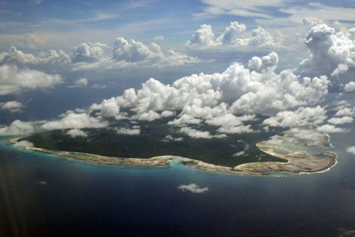 FILE ?- In this Nov. 14, 2005 file photo, clouds hang over the North Sentinel Island, in India's southeastern Andaman and Nicobar Islands. India used heat sensors on flights over hundreds of uninhabited Andaman Sea islands Friday, March 14, 2014, and will expand its search for the missing Malaysia Airlines jet farther west into the Bay of Bengal, officials said. The Indian-controlled archipelago that stretches south of Myanmar contains 572 islands covering an area of 720-by-52 kilometers. Only 37 are inhabited, with the rest covered in dense forests. (AP Photo/Gautam Singh, File)