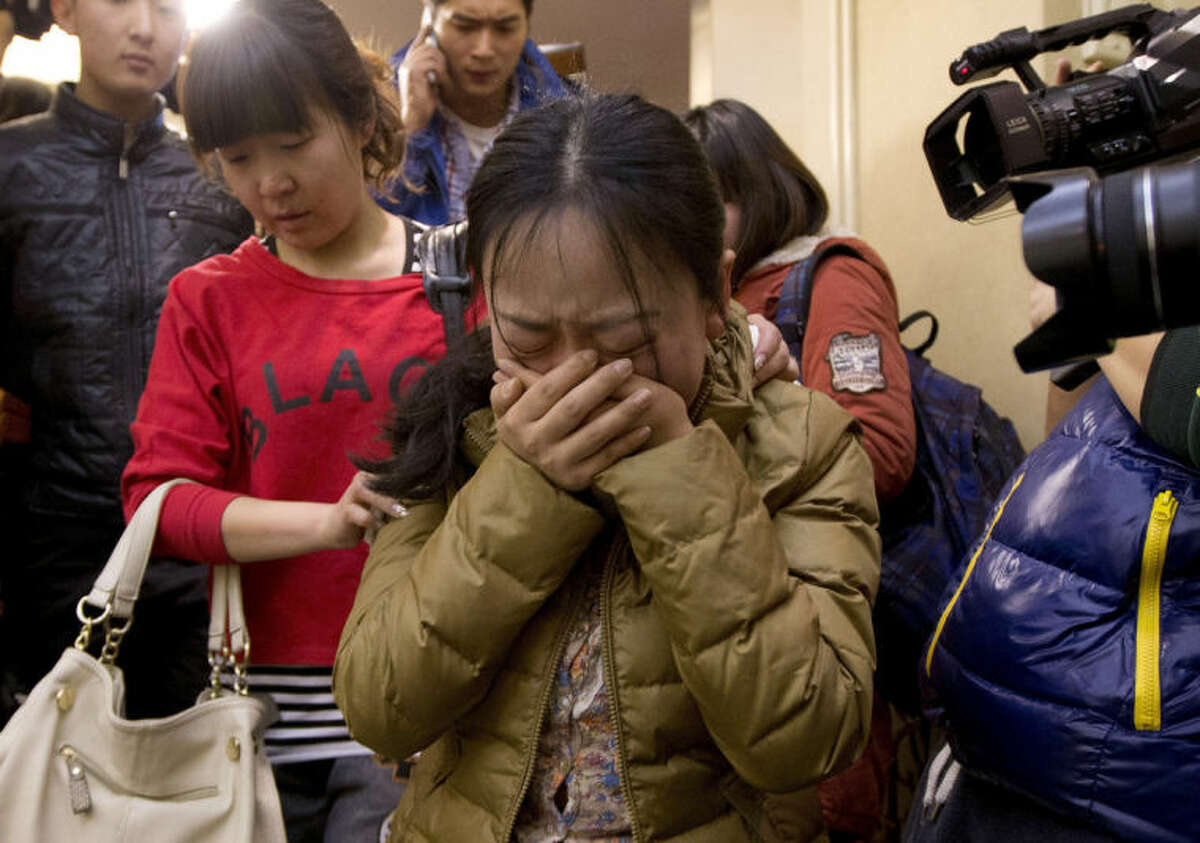 A Chinese relative of passengers aboard a missing Malaysia Airlines plane, center, cries as she is escorted by a woman while leaving a hotel room for relatives or friends of passengers aboard the missing airplane, in Beijing, China Sunday, March 9, 2014. Planes and ships from across Asia resumed the hunt Sunday for the Malaysian jetliner missing with 239 people on board for more than 24 hours, while Malaysian aviation authorities investigated how two passengers were apparently able to get on the aircraft using stolen passports. (AP Photo/Andy Wong)