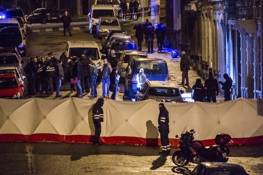 Belgian police officers gather behind a screen as they investigate a a shootout in an anti-terrorist raid in a street in Verviers, Belgium, Thursday, Jan. 15, 2015. Belgian authorities say two people have been killed and one has been arrested during a shootout in an anti-terrorist operation in the eastern city of Verviers. (AP Photo/Geert Vanden Wijngaert)