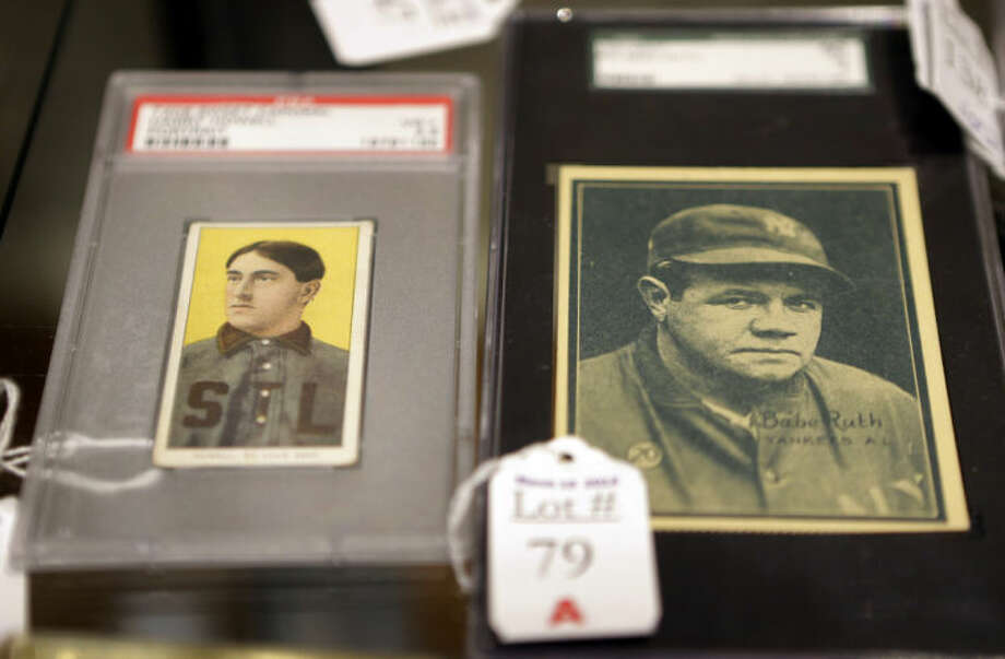 In this photo made Tuesday, March 11, 2014, baseball cards of major leaguers Harry Howell, left, and Babe Ruth are seen at the Saco River Auction House in Biddeford, Maine. The auction house is getting a reputation for selling some of the nation's oldest baseball memorabilia. (AP Photo/Robert F. Bukaty)
