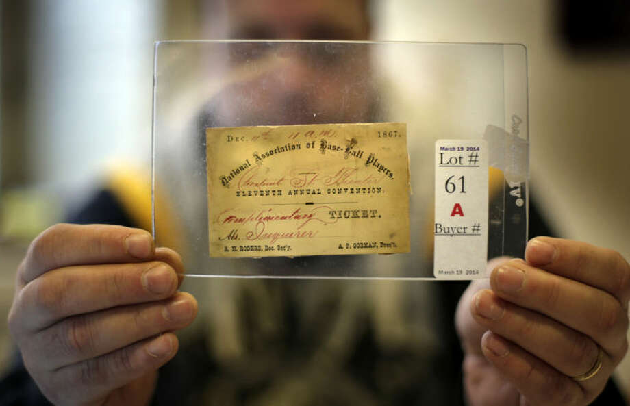 In this photo made Tuesday, March 11, 2014, an 1870 Philadelphia Athletics season ticket is held by Troy Thibodeau, manager of the Saco River Auction House in Biddeford, Maine. The card is 10 years older than anything on display at the Hall of Fame Museum. The auction house is getting a reputation for selling some of the nation's oldest baseball memorabilia. (AP Photo/Robert F. Bukaty)