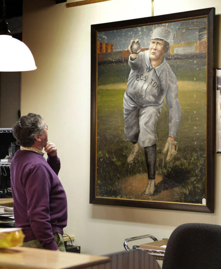 In this photo made Tuesday, March 11, 2014, auctioneer Floyd Hartford examines a 1910 painting of Cy Young in a Boston Red Sox uniform at the Saco River Auction House in Biddeford, Maine. The auction house is getting a reputation for selling some of the nation's oldest baseball memorabilia. (AP Photo/Robert F. Bukaty)