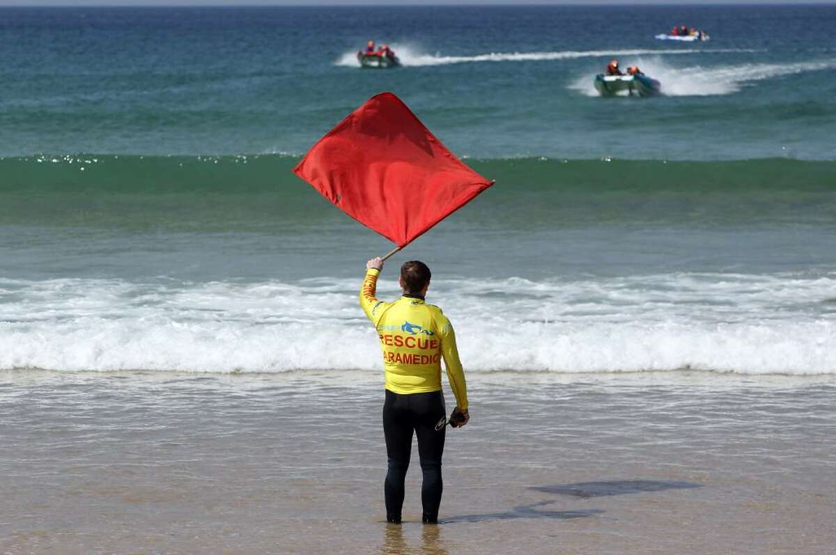 NEWQUAY, ENGLAND - APRIL 23: A red flag is waved from the beach as Zapcat power boats practice in the surf at Fistral Beach on April 23, 2010 in Newquay, England. Cornwall's Newquay is this weekend playing host to the Blue Chip Zapcat Grand Prix where small inflatable catamaran powerboats built for speed with 50hp engines, will battle it out in the national championship. (Photo by Matt Cardy/Getty Images)