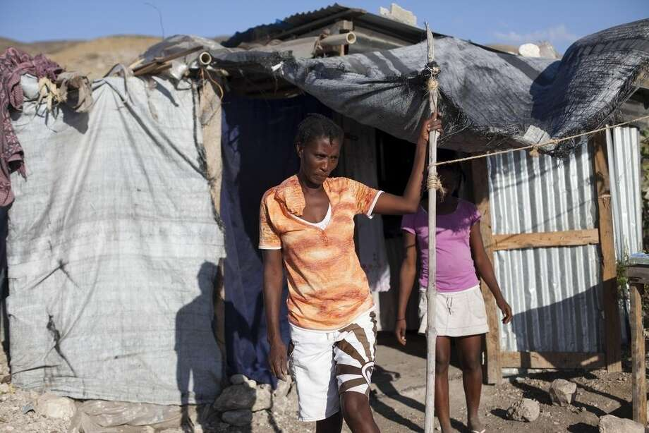 Rosena Dordor, 40, stands in front of her one-room shack in the arid hills north of the Capital in Port-au-Prince, Haiti, Friday, Jan. 9, 2014. Today, nearly five years after the devastating 7.0 earthquake that shook Haiti, Dordor lives with her husband and three children in a one-room shack with a plastic tarp for a roof and walls made of scrap metal and salvaged wood. It's perched on a cactus- and scrub-covered hillside, a long walk from the nearest source of water, and meals are cooked over fire pits. ( AP Photo/Dieu Nalio Chery)