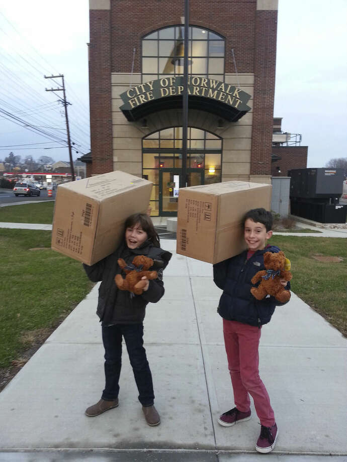 Contributed photoVladimir Romano, president of the Teddy Bear Fund, on left and Vice President Benen Blessey, on right, deliver donated Teddy bears to Norwalk Fire Department.