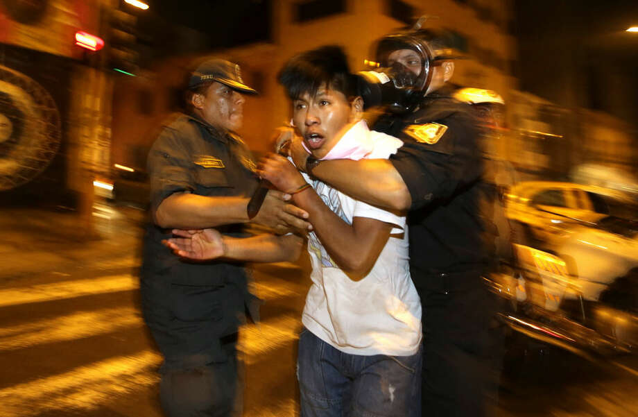 In this Thursday, Jan. 15, 2015 photo, police detain a youth who identified himself as a working student as he protests a new labor law that affects young workers in Lima, Peru. It was the fourth protest by youths in the last month since Peru's Congress approved in December a controversial law that eliminates some labor rights for workers age 18 to 24. The law takes away their right to severance pay, two annual bonuses, and reduces vacation time from 30 to 15 days per year. (AP Photo/Martin Mejia)