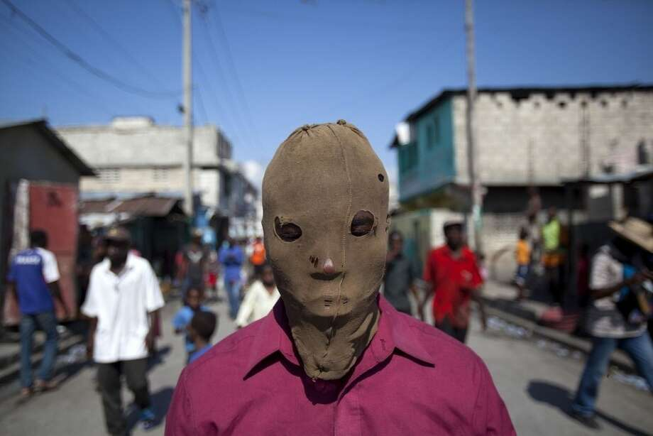 In this Saturday, Jan. 17, 2015 photo, a masked demonstrator takes part in a protest to demand the resignation of President Michel Martelly in Port-au-Prince, Haiti. The protest was the latest in a series of demonstrations demanding Martelly leave office before his term expires next year. (AP Photo/Dieu Nalio Chery)