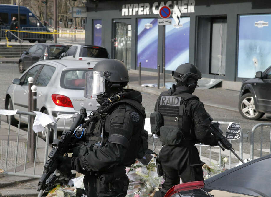 FILE - In this Monday Jan. 12, 2015 file photo,elite police officers take position outside the kosher market where four hostages were killed and shortly before Israeli Prime Minister Benjamin Netanyahu's visit to the site, in Paris. With the deaths of the three French officers during three days of terror in the Paris region and the suggestion of a plot in Belgium to kill police, European law enforcement agencies are rethinking how _ and how many _ police should be armed (AP Photo/Francois Mori, File)