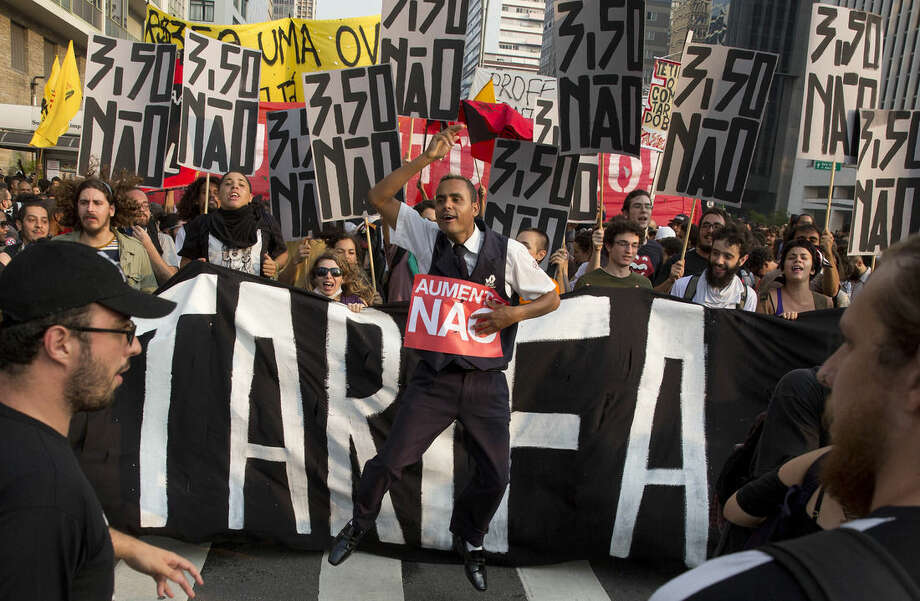 "In this Friday, Jan. 16, 2015 photo, demonstrators march with signs that read in Portuguese ""Increase no"" and ""3.50 no"" against the price hike on public transportation in Sao Paulo, Brazil. The price to use the subway and bus in Sao Paulo increased from 3.00 to 3.50 Reais on Jan. 5, about $1.30 US dollars. (AP Photo/Andre Penner)"