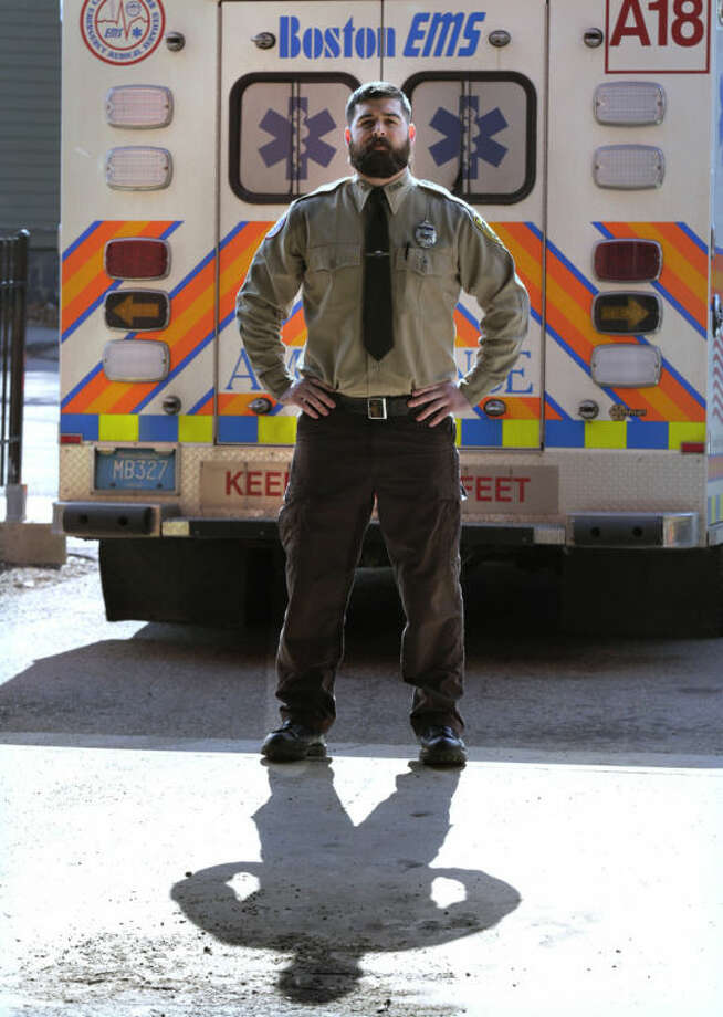 In this Thursday, March 20, 2014 photo, Boston Emergency Medical Services EMT Paul Mitchell stands next to an ambulance at his station in the Hyde Park neighborhood of Boston. Mitchell, along with bystander Carlos Arredondo and volunteer Devin Wang, are credited with helping to save the life of Jeff Bauman, who suffered traumatic injuries in the Boston Marathon bombings. (AP Photo/Charles Krupa)