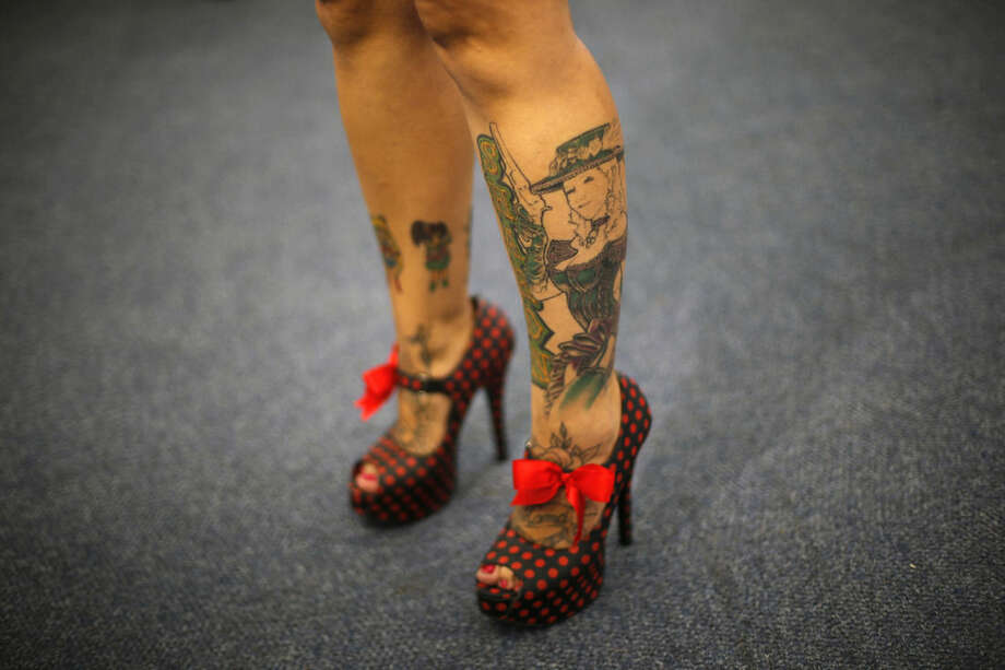In this Friday, Jan. 16, 2015 photo, a woman exhibits her tattoos and red ribbon polka dot shoes during Rio Tattoo Week in Rio de Janeiro, Brazil. Tattoo artists from Brazil and around the world gathered for the annual, three day convention. (AP Photo/Silvia Izquierdo)